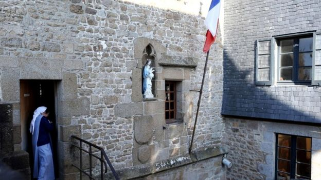 A nun of the Monastic of the Fraternities of Jerusalem leaves a polling station in Le Mont-Saint-Michel