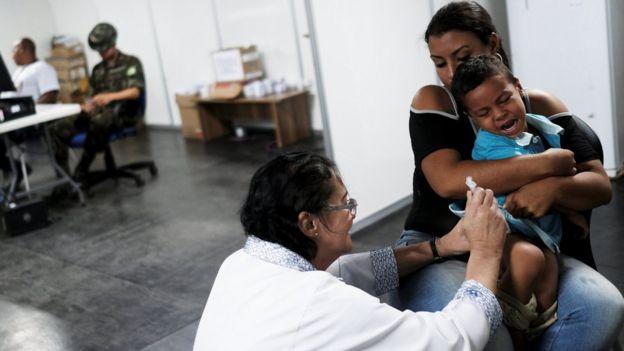 Criança toma vacina ao cruzar a fronteira da Venezuela com o Brasil