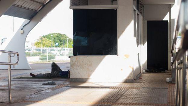 Pessoa deitada em estação abandonada do VLT