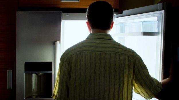 رجل يقف أمام ثلاجة الطعام