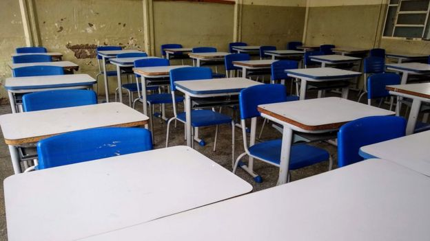 Cadeiras enfileiradas em sala de aula com paredes deterioradas