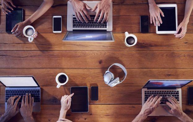 Grupo de millenials trabajando en sus laptops a escasa distancia.