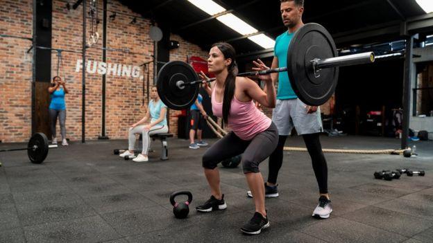 Mujer joven levantando pesas en un gimnasio