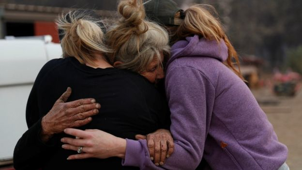 Cathy Fallon (C) who stayed behind to tend to her horses during the Camp Fire, embraces Shawna De Long (L) and April Smith who brought supplies for the horses in Paradise, California, U.S. November 11, 2018.