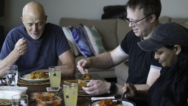 Tres personas comiendo en una mesas