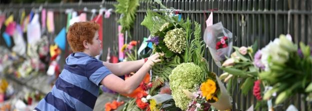 A child leaves a tribute at a memorial for victims in Christchurch