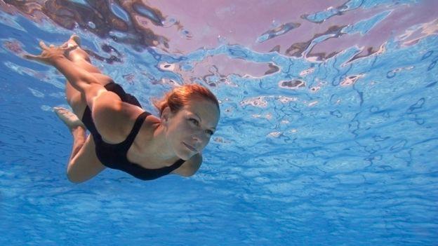 Mulher mergulhando com os olhos abertos