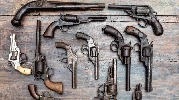 Diversas armas de fogo sobre mesa