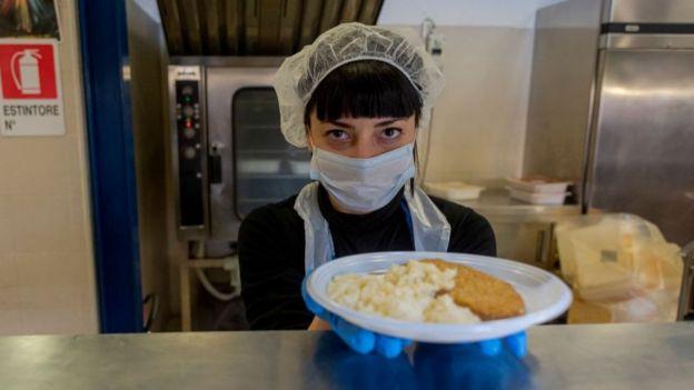 Voluntarios en Italia reparten comida a las personas que viven en la calle.