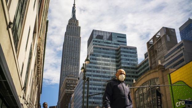 A man wears a face mask as the city streets are empty due to the coronavirus in New York City on 24 March 2020