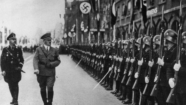 Himmler y Hitler caminan frente a un comando de la SS en 1938.