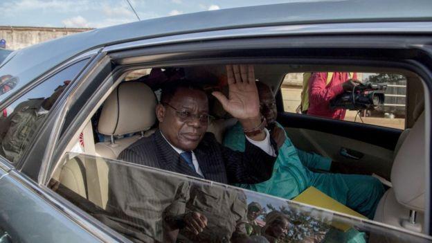 Maurice Kamto fait signe de la main à ses militants depuis sa voiture.