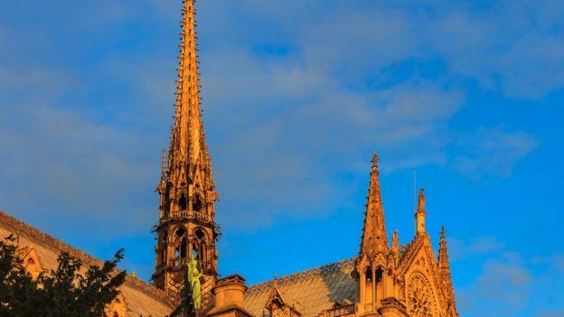 Imagem da torre agulha em Notre Dame, antes do incêndio, sob a luz amarelada do pôr do sol