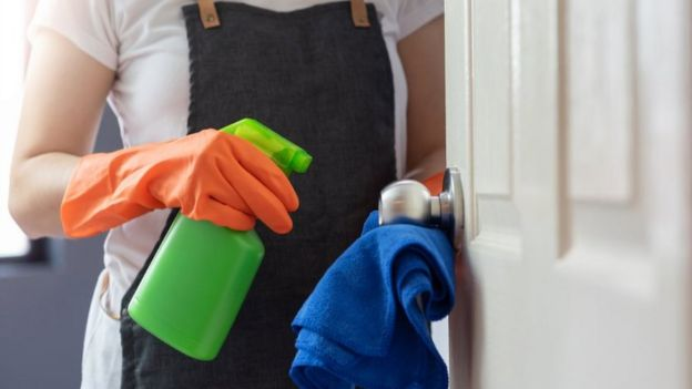 Female hands in orange rubber gloves cleaning on touching surface of door, doorknob with blue microfiber cleaning cloth and green spray bottle - stock photo