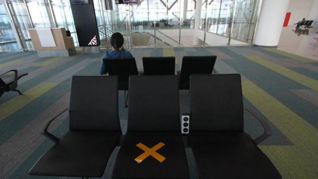 Calon penumpang duduk menunggu jadwal keberangkatan pesawat di Terminal Bandara Internasional Syamsudin Noor, Banjarbaru, Kalimantan Selatan, Kamis (19/03).