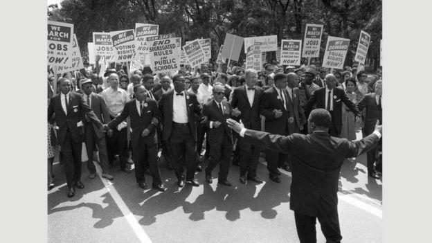 """مارتن لوثر كينغ الابن مع عدد آخر من قادة حركة الدفاع عن الحريات المدنية يتقدمون ما عُرِفَ باسم """"المسيرة إلى واشنطن من أجل الحرية والوظائف"""" في 28 أغسطس/آب 1963"""