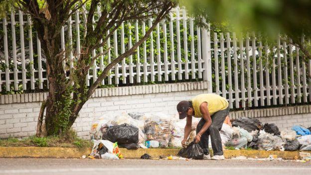 Persona en Venezuela buscando comida en la basura.