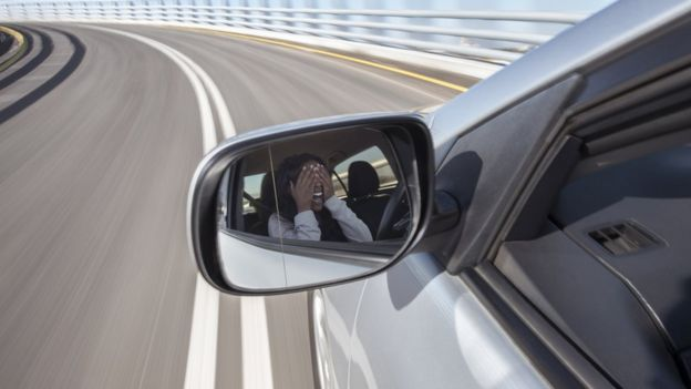 Woman covering her eyes in a car that is traveling at high speed.