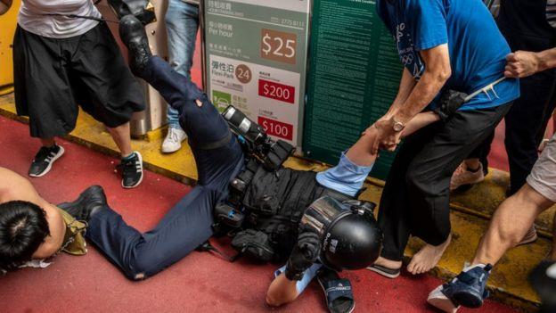Người dân Hong Kong lôi kéo một sĩ quan cảnh sát khi lực lượng cảnh sát bắt giữ một số người biểu tình tại Kowloon Bay hôm 24/9 sau khi nhiều người ủng hộ Bắc Kinh xô xát với người biểu tình ở khu trung tâm thương mại
