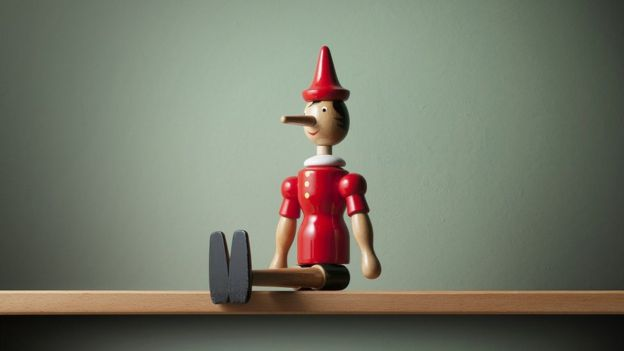 A wooden Pinocchio figurine, sitting on a shelf
