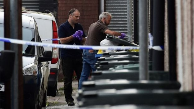 Investigators search rubbish bins behind a police cordon
