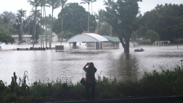 A woman takes photos of floodwaters from Hurricane Lane rainfall on the Big Island, Hawaii, 23 August 2018