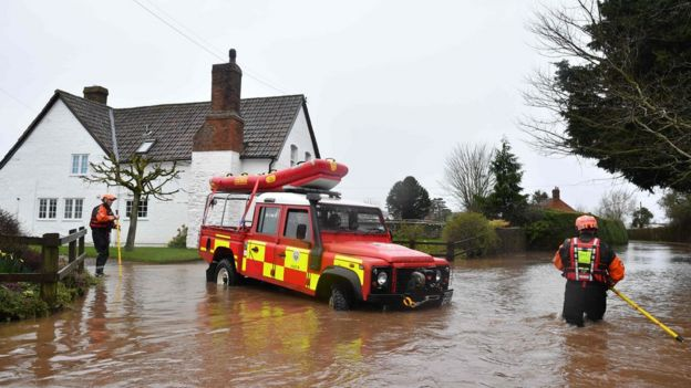 Hereford Fire and Rescue personnel reverse their vehicle as water becomes too deep amid flooding in the village of Hampton Bishop in Herefordshire, western England