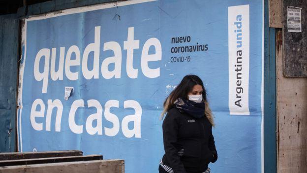 """Una mujer camina frente a un cartel que dice """"quedate en casa"""" en Buenos Aires"""