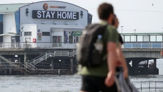 People walk past a sign saying 'Stay Home' projected from Bournemouth pier