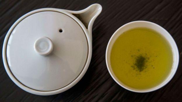 Vasija con té y un pocillo con té verde servido.