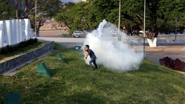"A man reacts to tear gas near the Generalisimo Francisco de Miranda Airbase ""La Carlota"", in Caracas, Venezuela April 30, 2019."