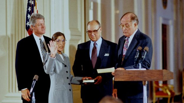 Justice Ginsburg is sworn in, with her husband Martin holding the bible