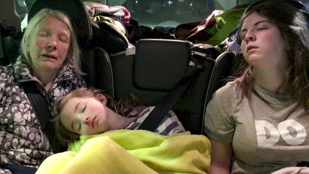 Niña, adolescente y señora durmiendo en auto.