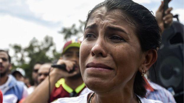 Una mujer venezolana llora durante una ceremonia de llegada de ayuda a la frontera entre Venezuela y Colombia