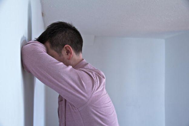 Hombre apoyado contra una pared