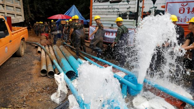 Soldiers and rescue workers walk past water pumped out of Tham Luang cave complex