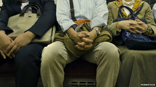 A man sitting between two others on a train