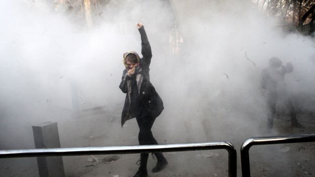 An Iranian university student raises her fist in a cloud of smoke at Tehran University. This image of a female protestor was one of the images widely shared on social media during recent protests