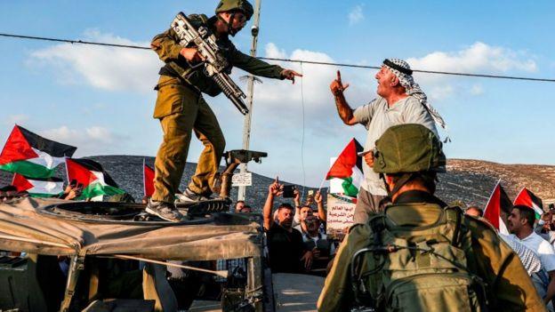 Homem brigam, um deles fortemente armado, em meio a bandeiras da Palestina e outros