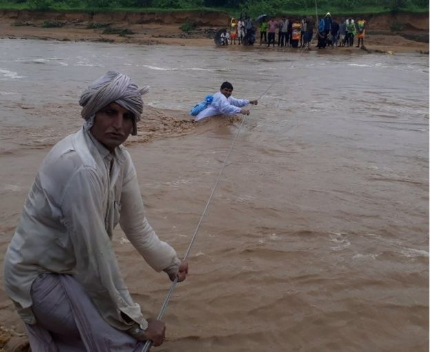 This photo taken on July 25, 2017 shows Indian men trying to cross flood waters in Deesa municipality, which has been hit by severe flooding along the Banas River in northern Gujarat state in western India