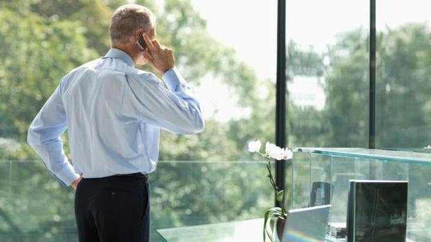 Hombre de negocios mirando por la ventana mientras habla por teléfono