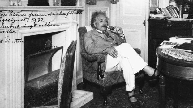 Albert Einstein, sentado, en sandalias