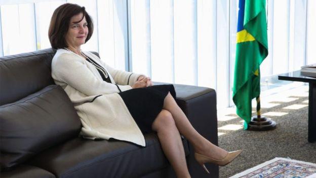 A procuradora Raquel Dodge sentada em um sofá escuro ao lado de uma bandeira do Brasil