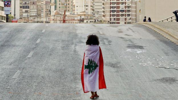 امرأة تغطي نفسها بعلم لبنان