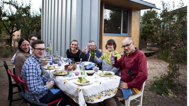 Na foto, Bobby (C, de jaqueta azul) e membros da vizinhança em frente à primeira microcasa construída em projeto que estimula americanos a permitirem a instalação dessas moradias no quintal de suas casas para abrigar pessoas até então sem-teto
