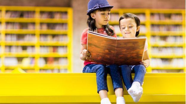 Duas crianças olham para livro