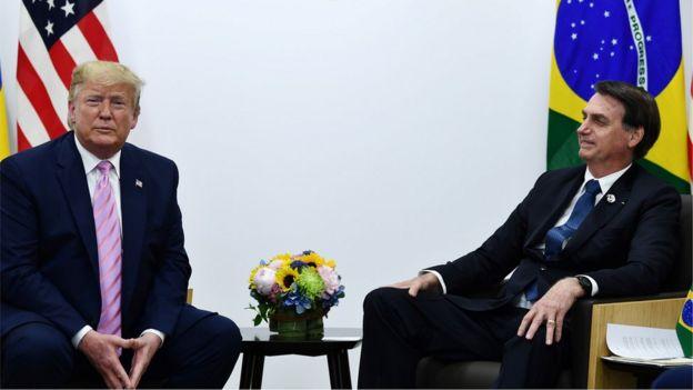 Presidente americano Donald Trump e presidente brasileiro Jair Bolsonaro sentados em sala de reunião, com bandeiras de seus respectivos países atrás