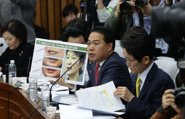 Opposition People's Party lawmaker Lee Yong-Joo shows impeached President Park Geun-Hye's three pictures combo taken on May during a parliamentary hearing over the Choi Soon-sil gate probe at the National Assembly on December 14, 2016 in Seoul, South Korea.
