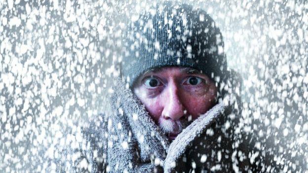 Una persona abrigada con nieve a su alrededor.