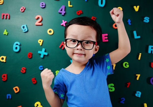 Cute little boy in front of a dark green chalkboard, with colourful magnetic numbers stuck on it